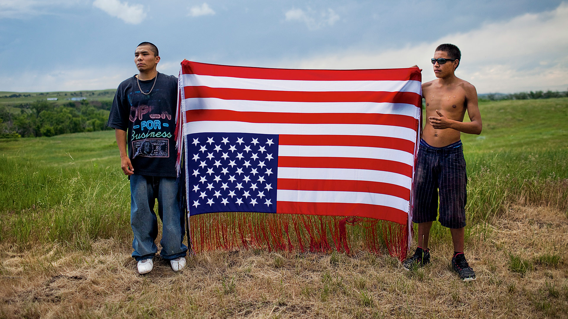 © Aaron Huey. Oglala youths hold an upside-down flag, an international symbol of distress and an act of defiance toward the U.S. government, at a rally to commemorate a 1975 shoot-out between American Indian Movement (AIM) activists and FBI agents. Two agents and one AIM member died; AIM�s Leonard Peltier was jailed for life. | Festival della Fotografia Etica 2016 - Lodi, 8 - 30 ottobre 2016