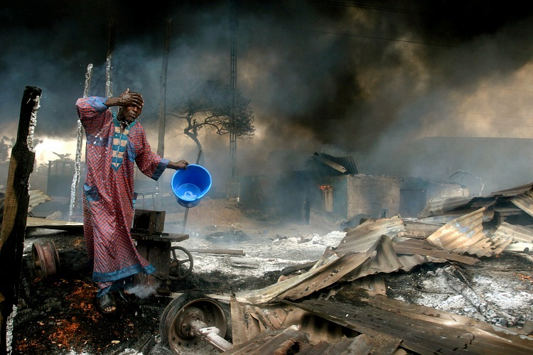 Akintunde Akinleye, Un uomo si lava il viso sul limitare del sito dove è esploso un gasdotto a Lagos. Dei ladri avevano cercato di perforare il gasdotto sotterraneo. Primo Premio Spot News al World Press Photo 2007. © Akintunde Akinleye/Reuters.