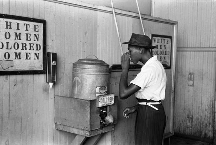 Russell Lee, Negro mentre beve dell'acqua a una fontanella refrigeratrice per gente di colore al capolinea dell'autobus. Oklahoma City, Oklahoma, U.S.A., luglio 1939. © Russell Lee. Courtesy Farm Security Administration - Office of War Information Photograph Collection/Library of Congress