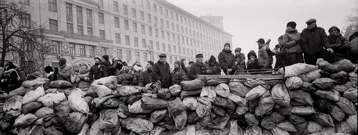 Pavel Wolberg, Ukrainian civilians stand behind a barricade as they watch riot police