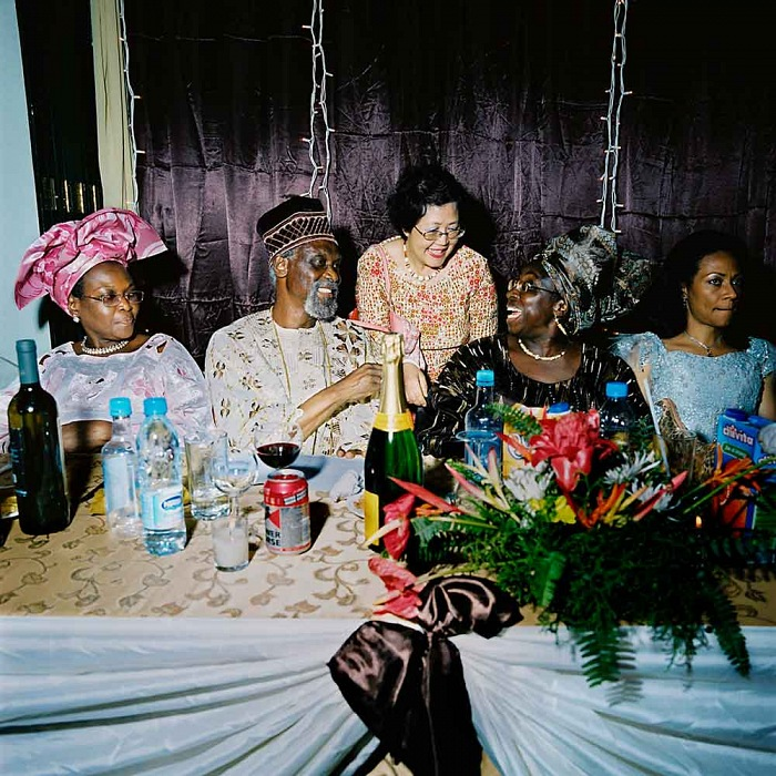 Nigeria, Lagos, 2007. Mrs. Wood in her immense restaurant, the 5 floors, 1500 seats Golden Gates of Lagos. The senator, Anthony Mogbongubola Soetan (on the left of the Champagne bottle) has come here to celebrate his 70th birthday in the company of about 300 guests, all members of the Nigerian elite. © Paolo Woods/Anzenberger, dalla serie Chinafrica