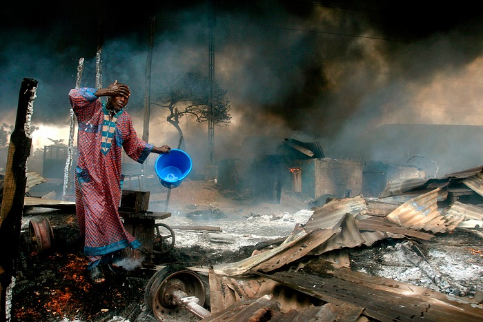 Akintunde Akinleye, A man rinses soot from his face at the scene of a gas pipeline explosion near Nigeria's commercial capital Lagos, December 26th, 2006. © Akintunde Akinleye/Reuters