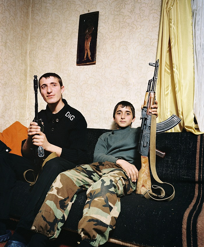 Rob Hornstra, Brothers Zashrikwa (17) and Edrese (14) pose proudly with a kalashnikov on the sofa in their aunt and uncle's house, Kuabchara, Abkhazia, 2009. © Rob Hornstra/Flatland Gallery