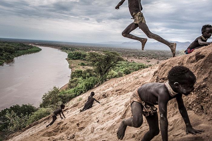 Fausto Podavini, I bambini di etnia Karo giocano nella sabbia sulle rive del fiume Omo, Etiopia, 2011, dalla mostra La fin d'un monde in esposizione allo Chemin des libellules nell'ambito di Festival Photo La Gacilly 2018. © Fausto Podavini.