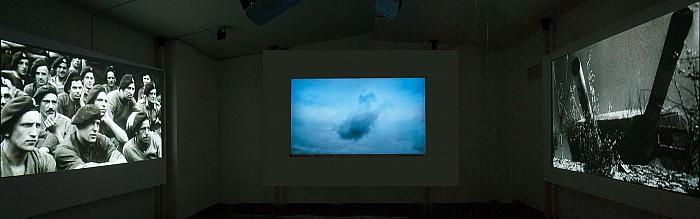 La sala dove vengono proiettati in contemporanea su tre schermi filmati d'epoca e riprese effettuate con il drone per accompagnare la mostra War Sand - June 6, 1944: D-Day di Donald Weber. © FPmag.