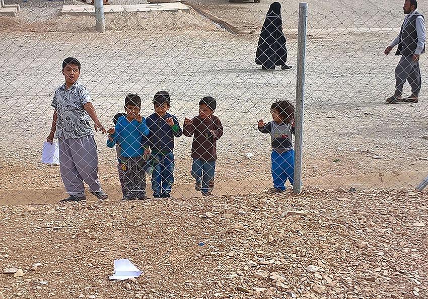 Bambini che giocano con un aeroplanino di carta finito al di là delle recinzioni del campo profughi che si trova accanto all'ospedale di Emergency a Sulaymaniyah in Kurdistan. © Piero Ingrosso.
