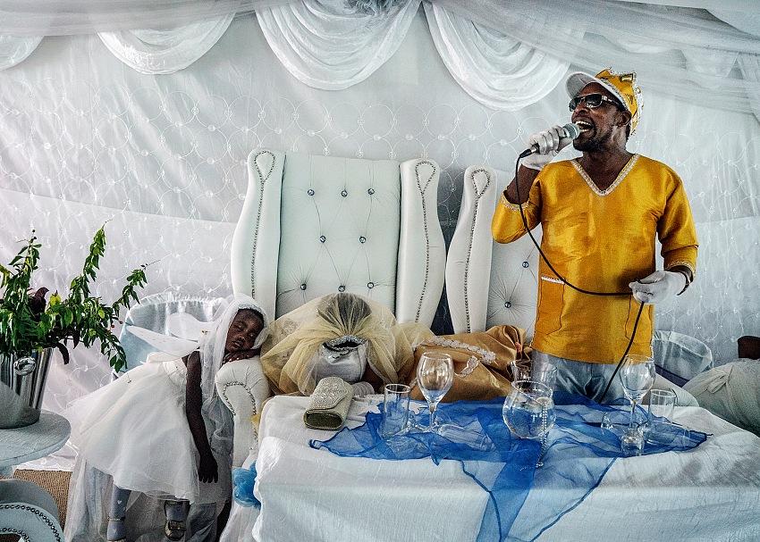 Jonas Bendiksen, Mosè Hlongwane, conosciuto anche semplicemente come Gesù, tiene un sermone al suo matrimonio con Angel, uno dei suoi discepoli. Nella teologia di Mosè, il giorno del suo matrimonio segna l'inizio dei tempi finali. Sudafrica, 2016. Courtesy Jonas Bendiksen/Magnum Photos.
